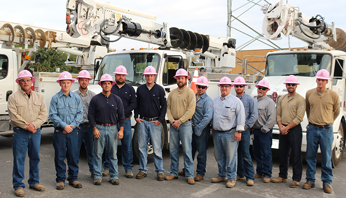 men in jeans and shirts with pink hard hats standing in front of bucket trucks