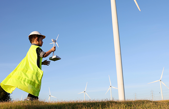 boy playing with windmill in field