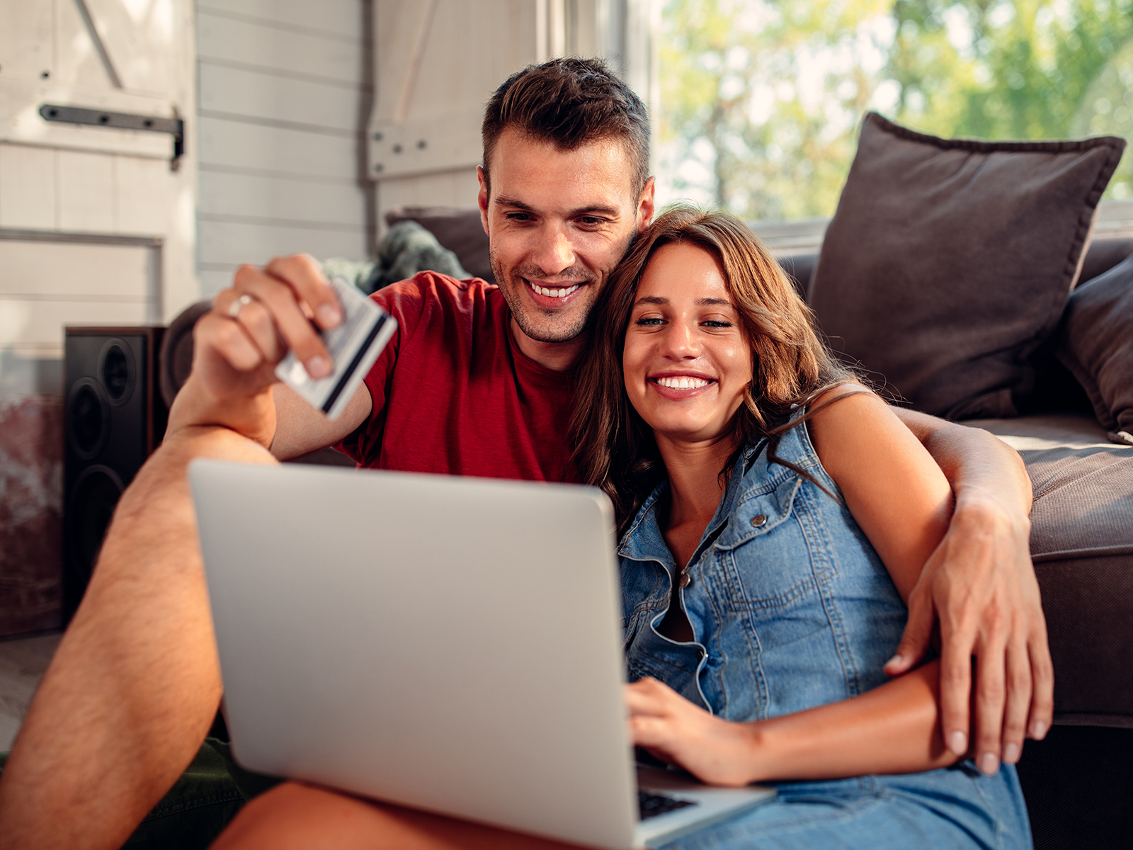 couple sitting together looking at laptop happily