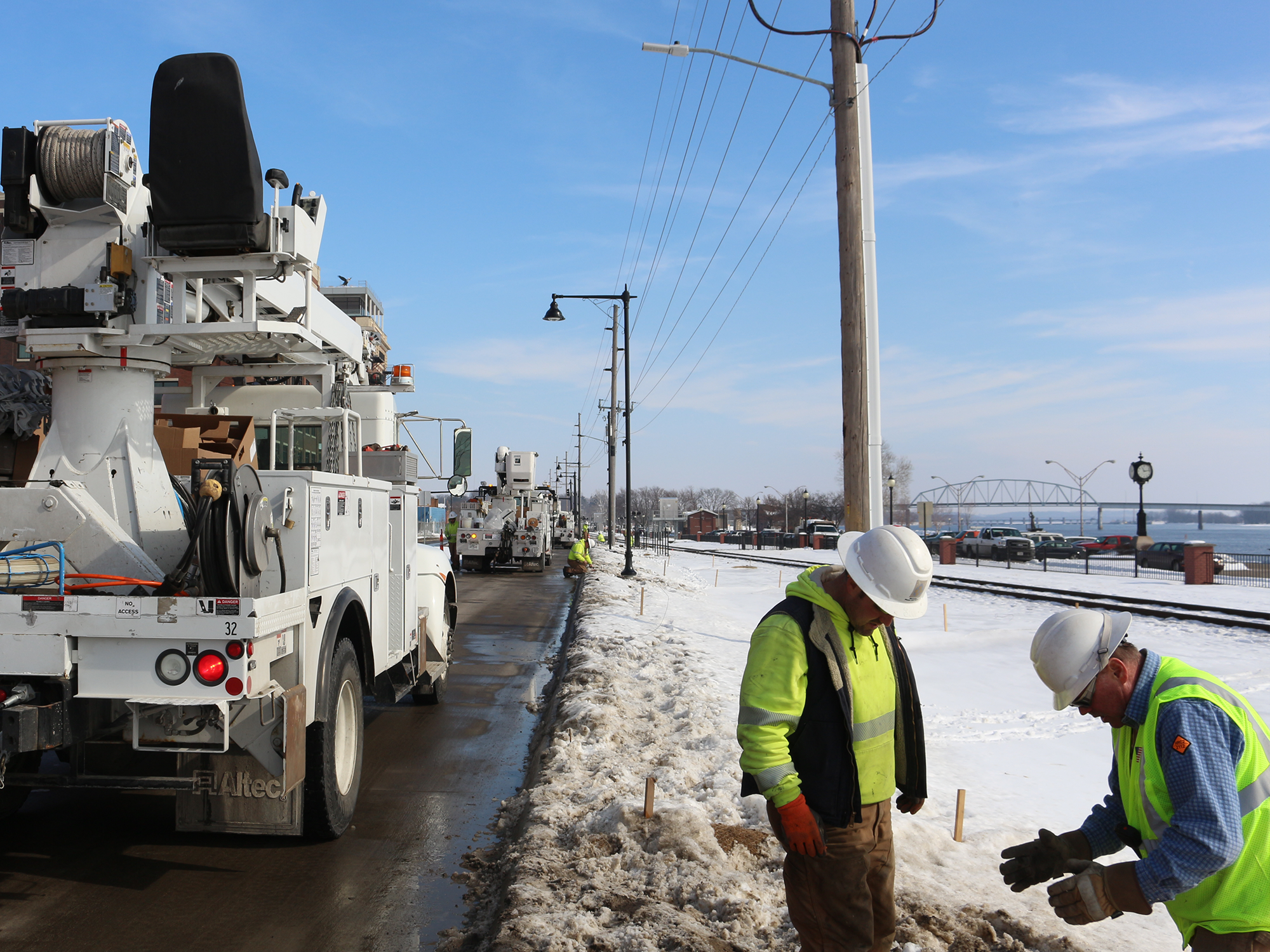 men working in snow on ground near electric pole