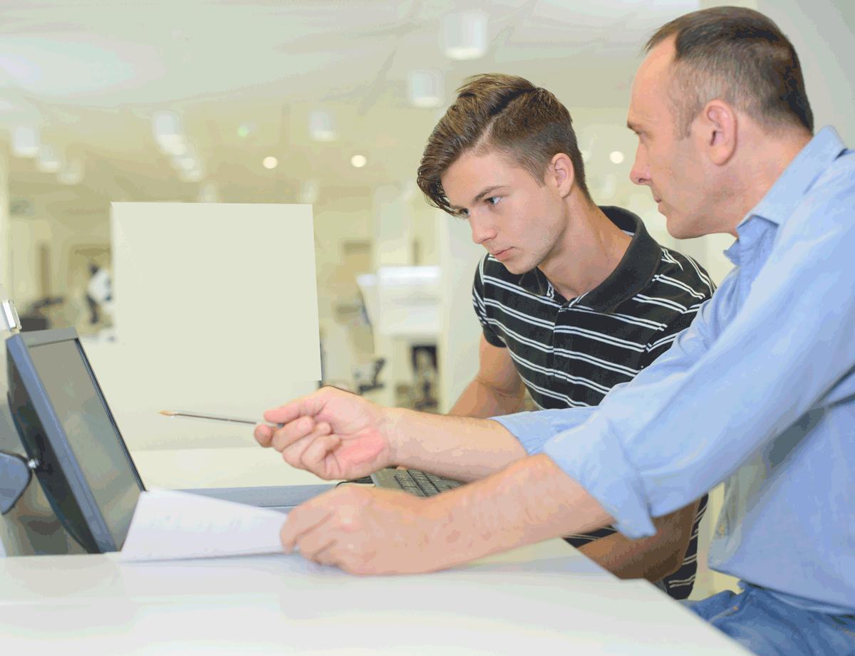 man teaching student at computer