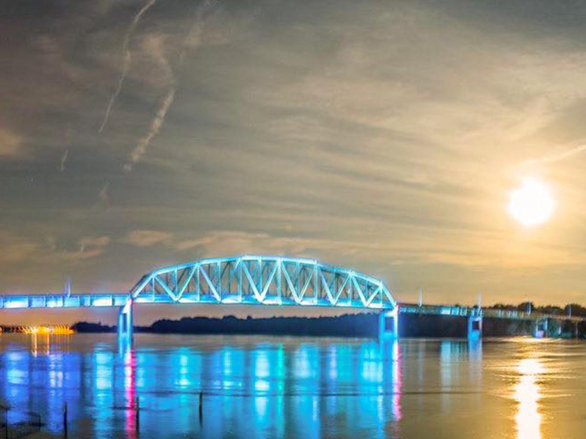 blue lit muscatine bridge on river