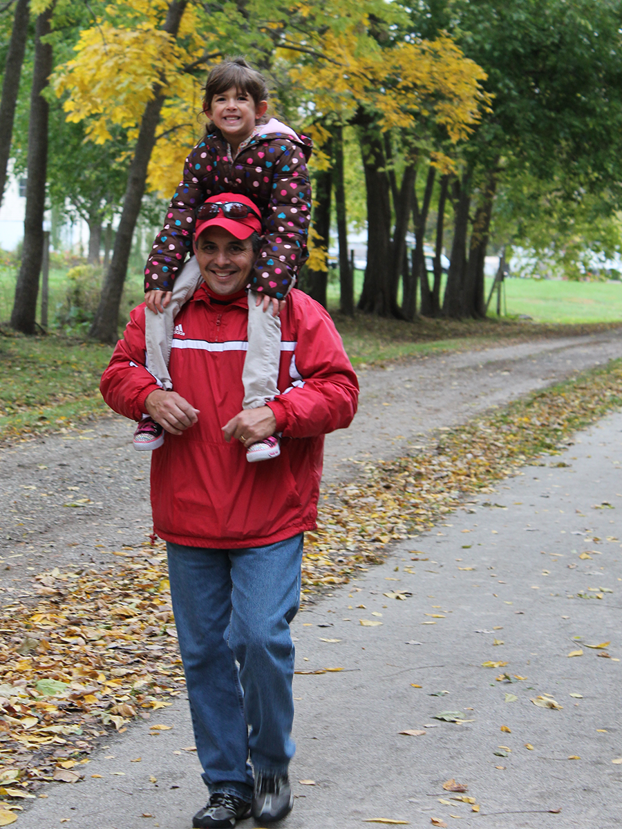 man walking on path with child on shoulders