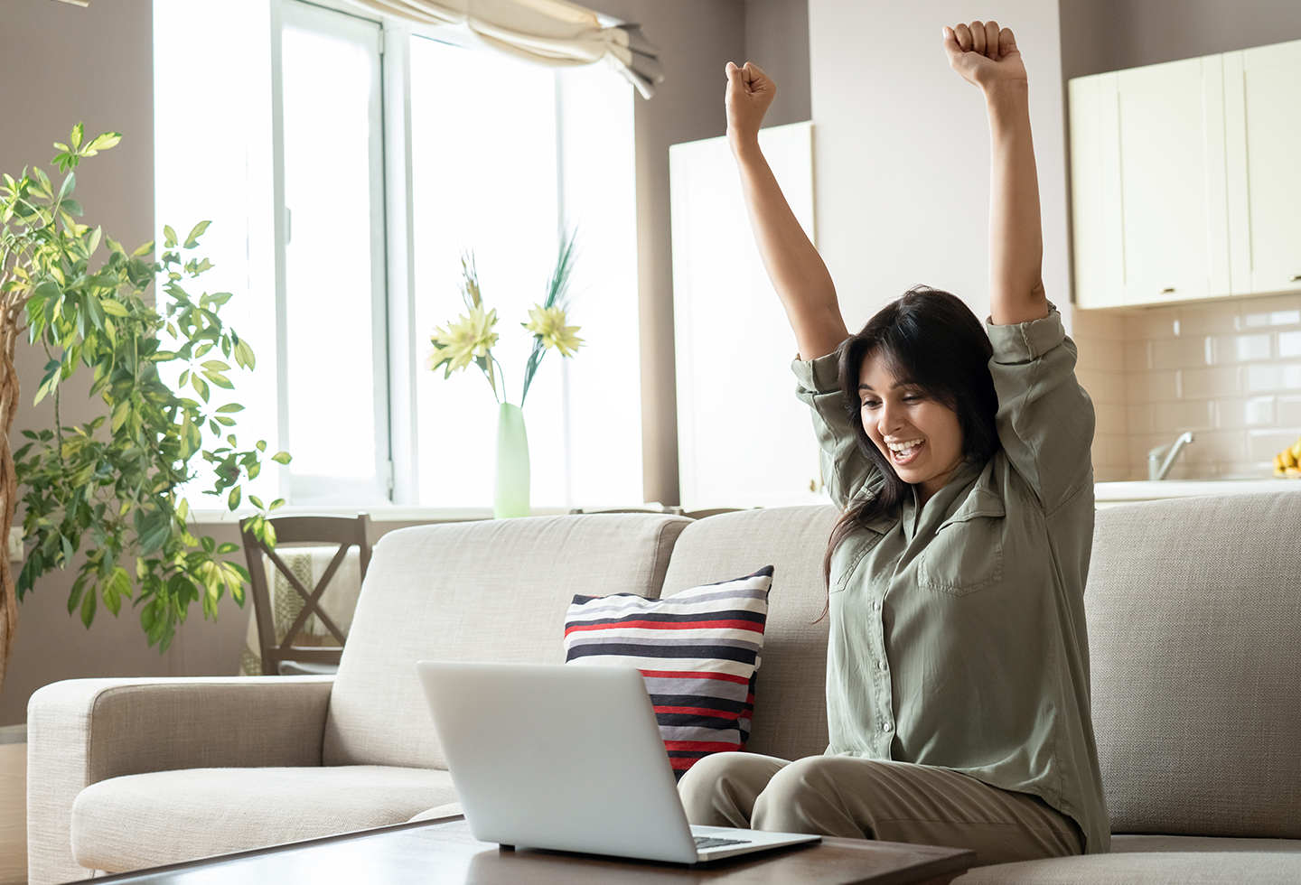 woman throwing hands in air in joy in front of computer