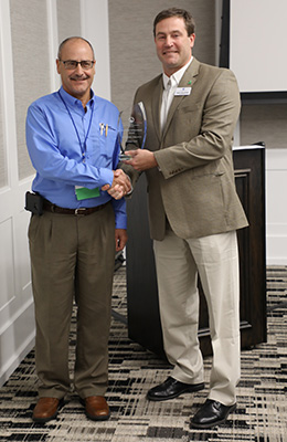 Two Men Standing Next to Each Other Shaking Hands, One Receiving Award