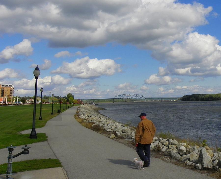 man walking dog on riverfront path