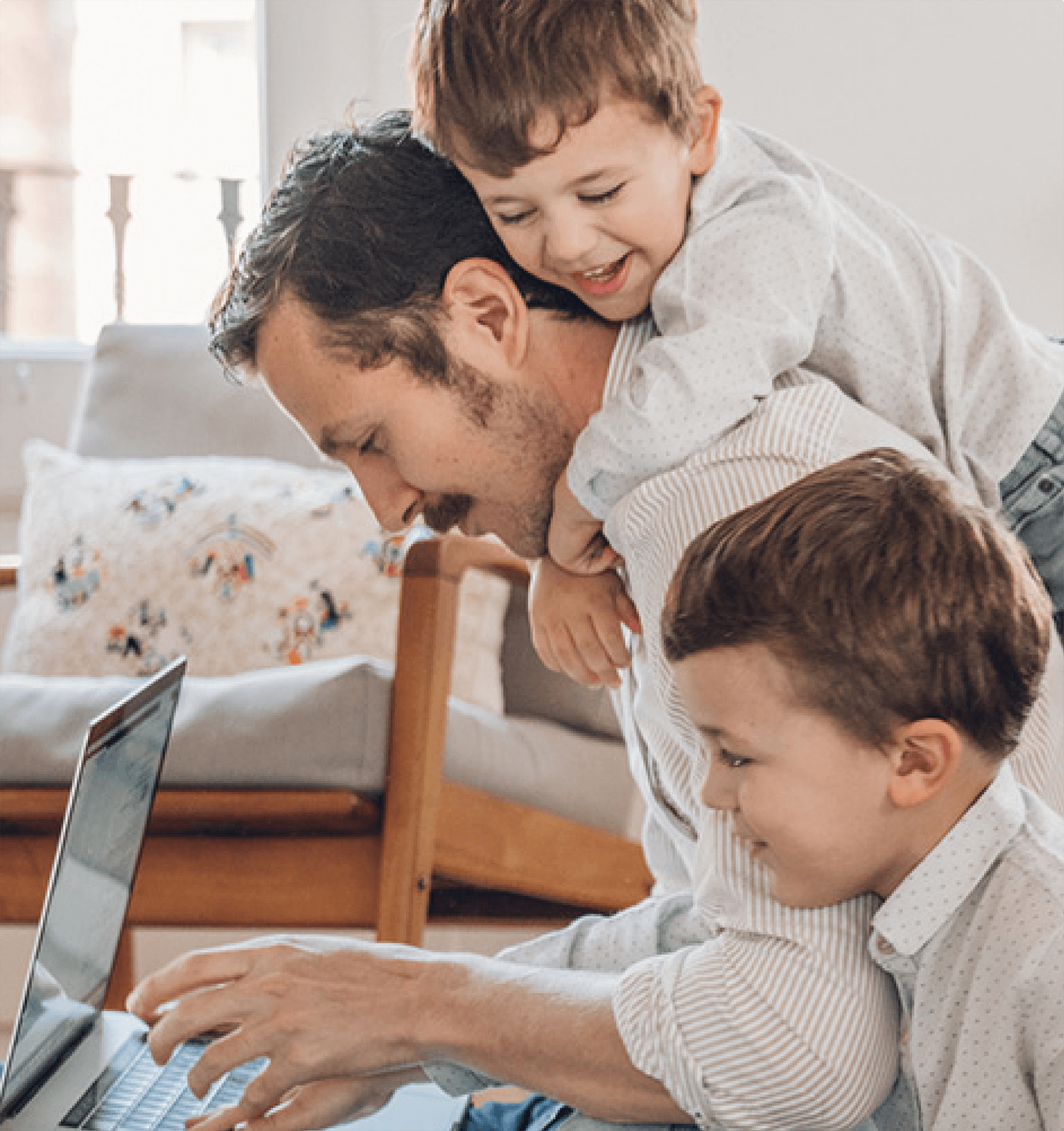 man on computer with 2 male kids climbing on hime