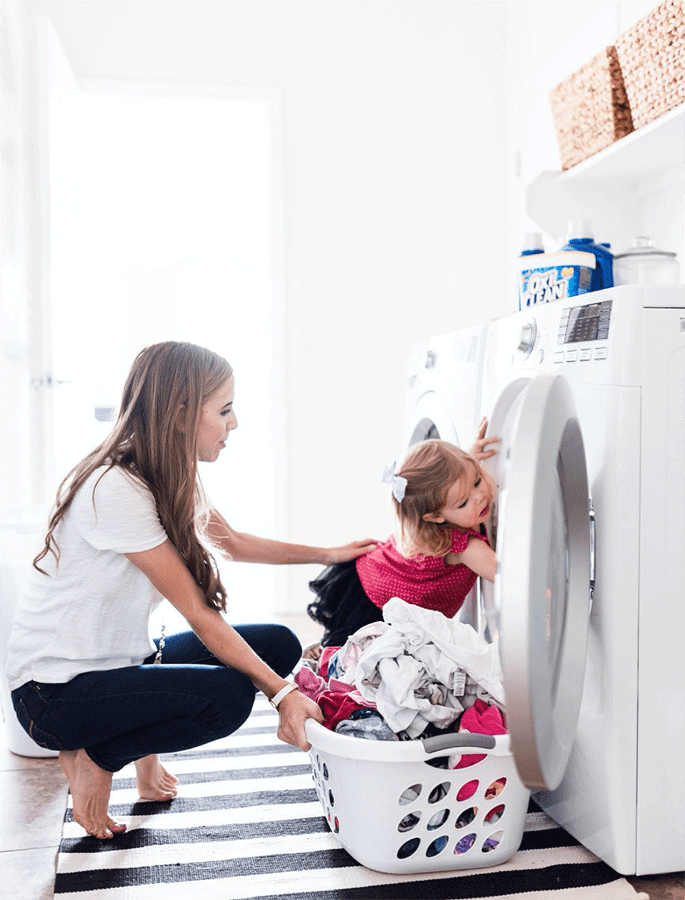 child and mother doing laundry