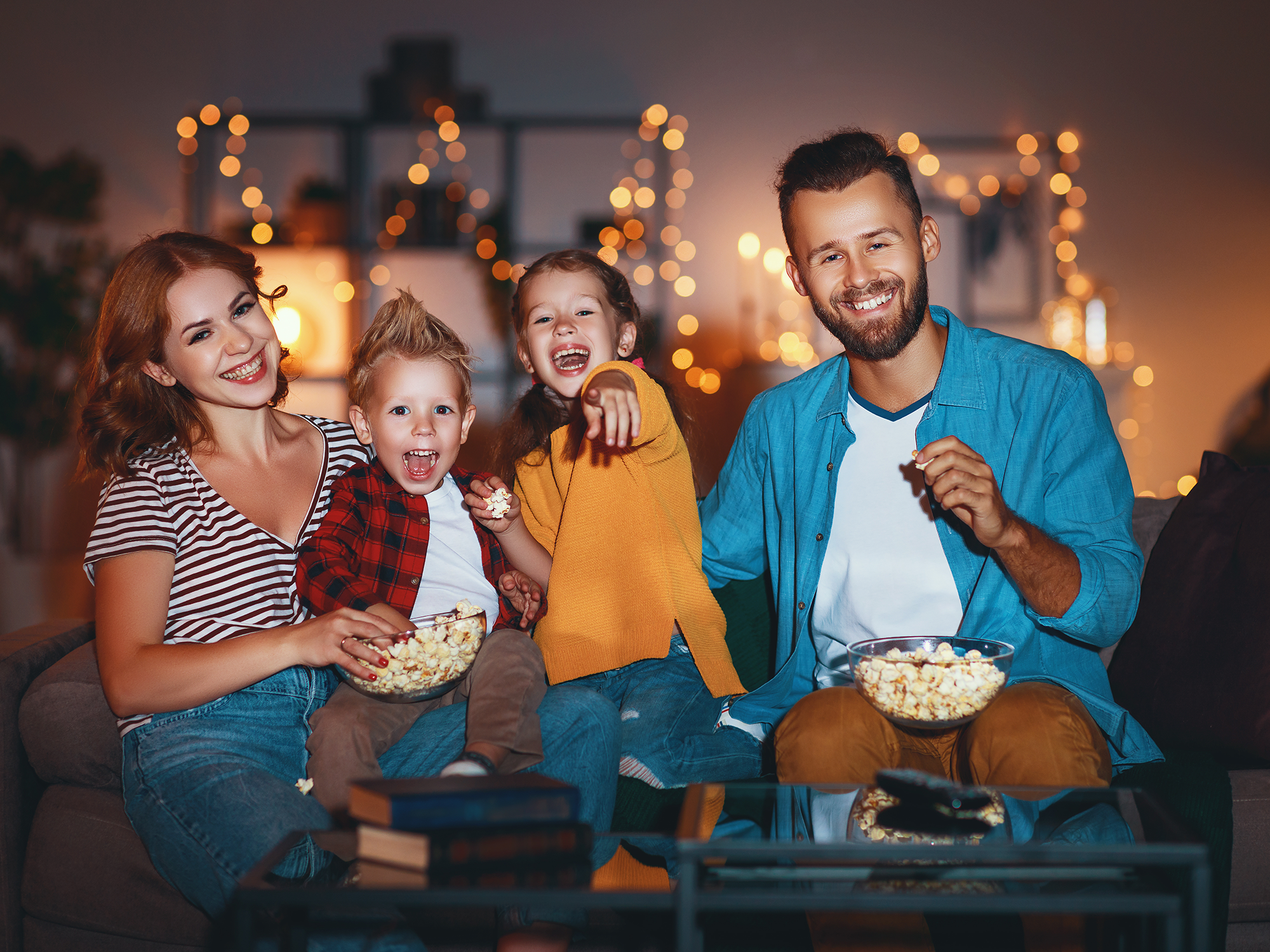 family sitting on couch watching tv and eating popcorn
